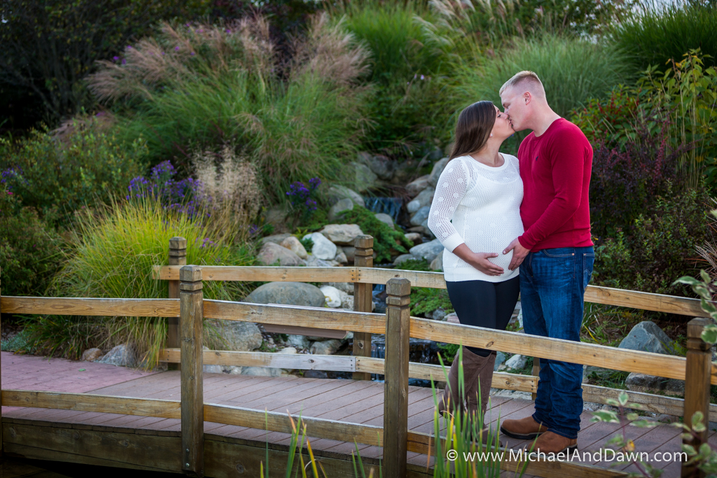 picture of pregnant couple kissing on bridge