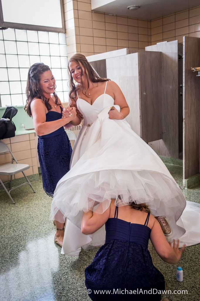 picture of bridesmaid under the bride's skirt