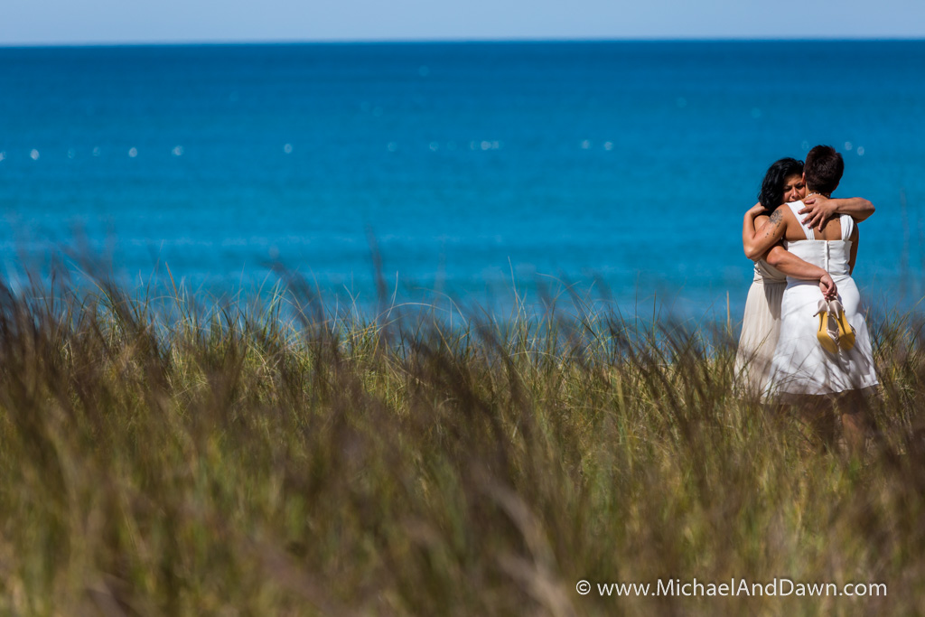 picture of two brides embracing in the sea grass by the shore