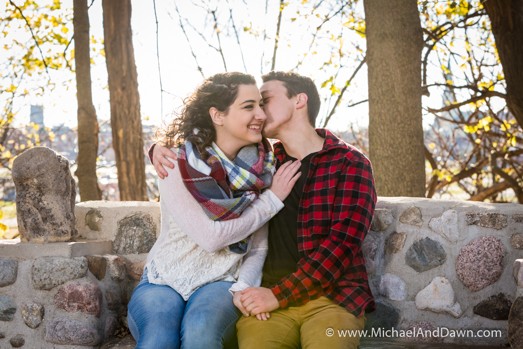 picture of and engagement kiss sitting on a rock bench