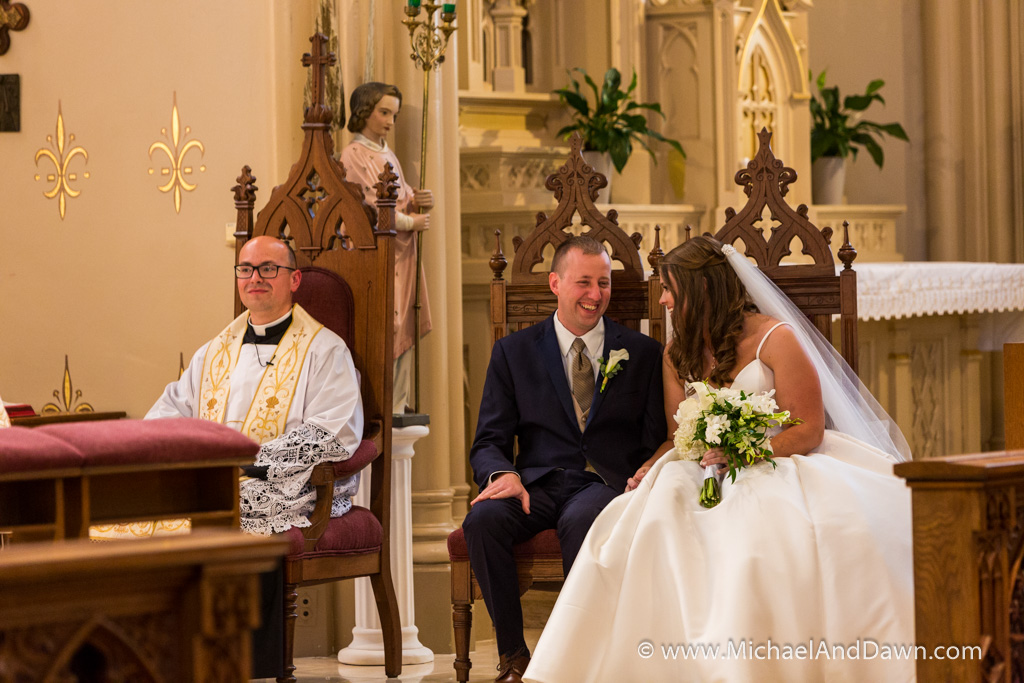 picture of bride and groom giggling on the alter