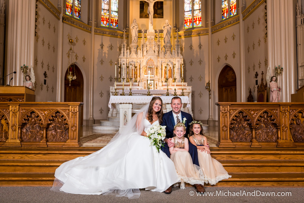 picture of the bride and groom with the flower girls sitting at the alter
