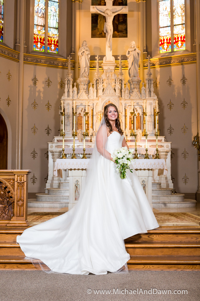 picture of bride showing wedding dress and flowers on the alter