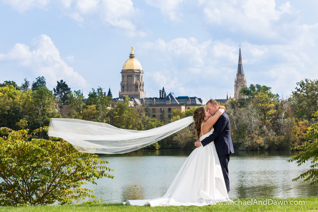 picture of bride and groom in front of the University of Notre Dame and Sacred Hart Church