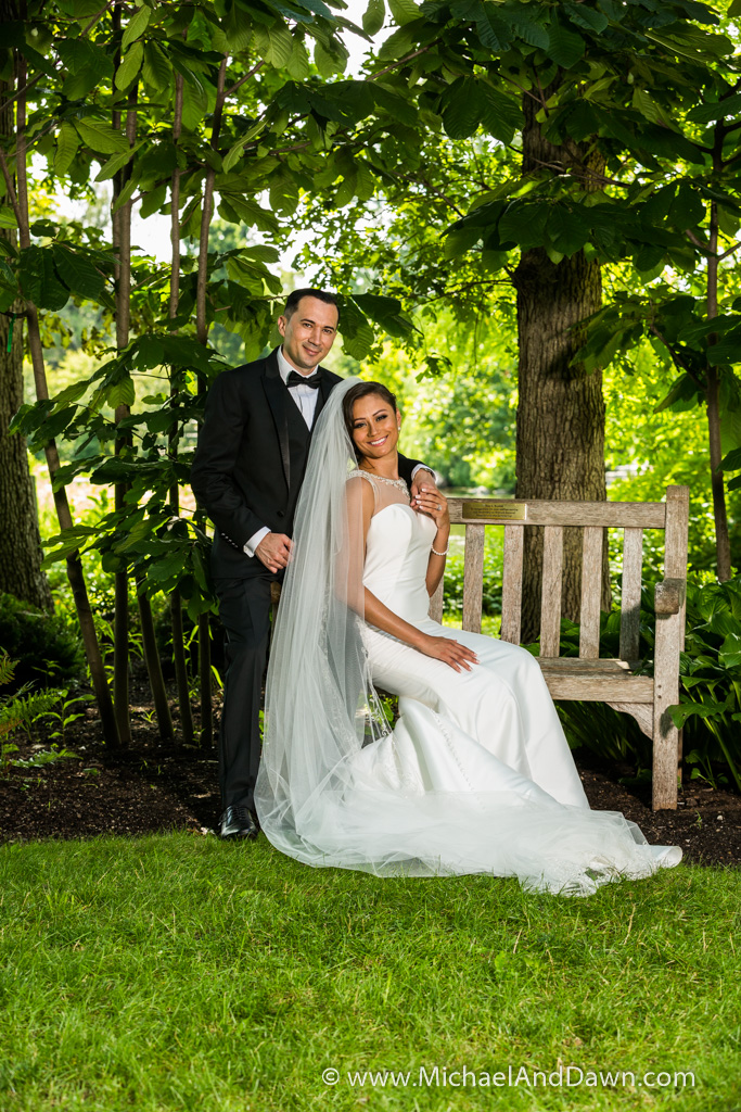 picture of bride sitting on bench with groom standing