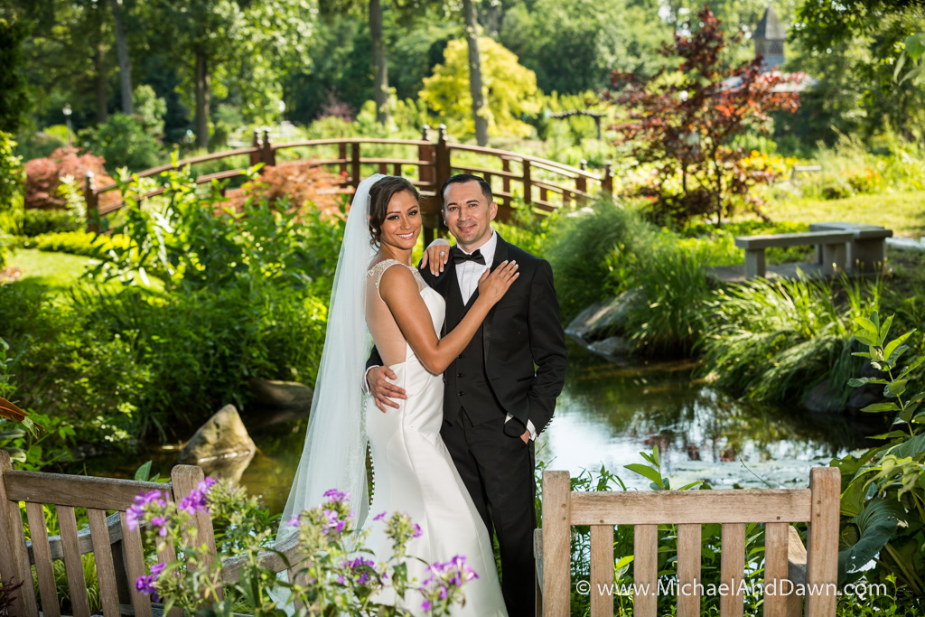picture of wedding couple with pond and bridge in background