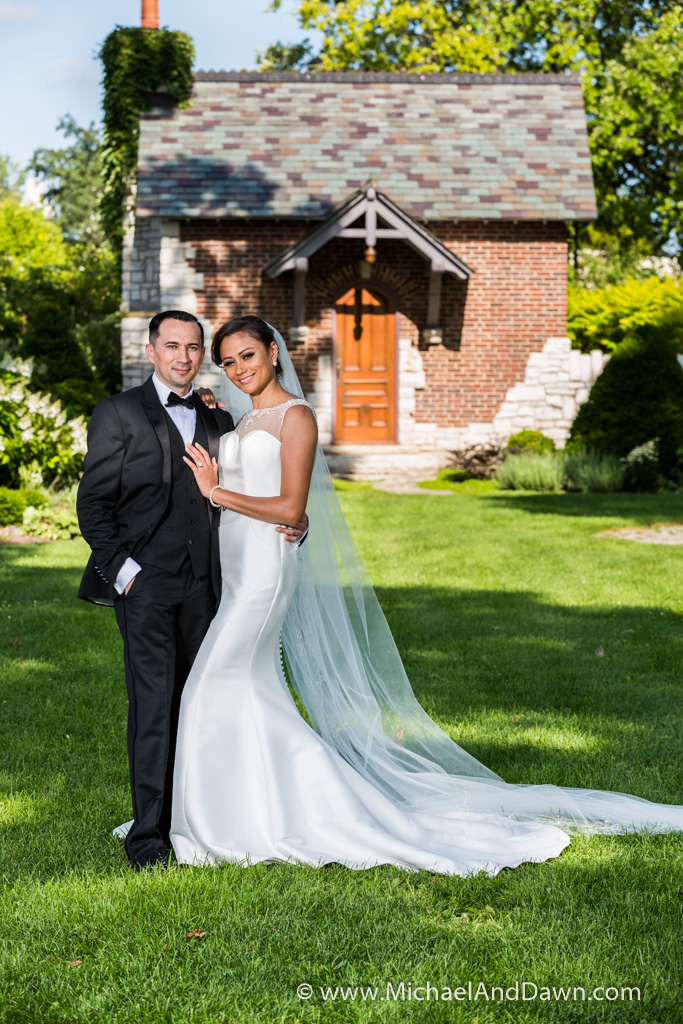 picture of groom and bride in front of little brick building
